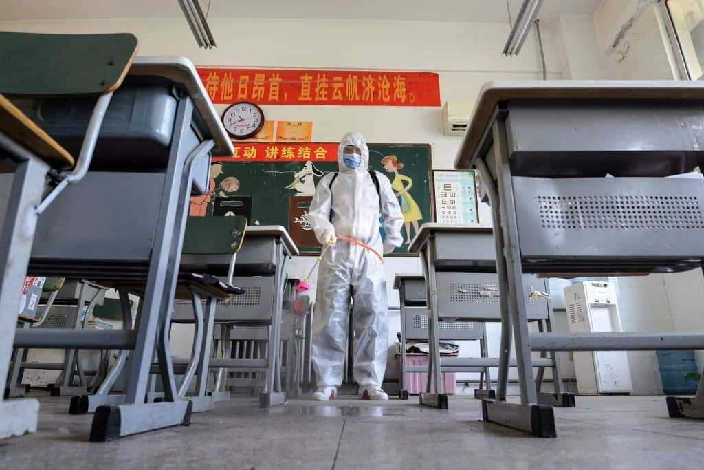 A staff member sprays disinfectant in a classroom of a school as it prepares to reopen after the term opening was delayed due to the COVID-19 coronavirus outbreak, in Handan in China's northern Hebei province